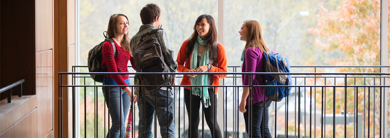Group of students talking near a railing